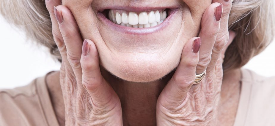 close up of an older woman holding her cheeks and smiling with dentures