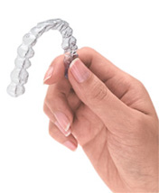close up of a hand holding a clear dental aligner