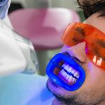 male teeth whitening patient getting in office light-activated treatment