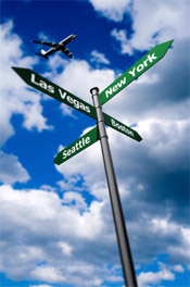 airplane flying over street signs for cities