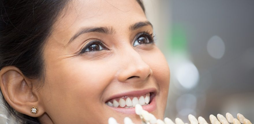 Smiling woman using shade guides for teeth whitening